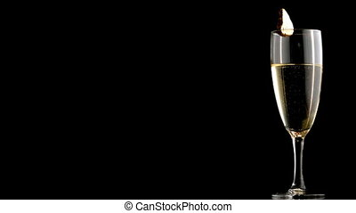 Champagne with ice cube falling into flute on black...