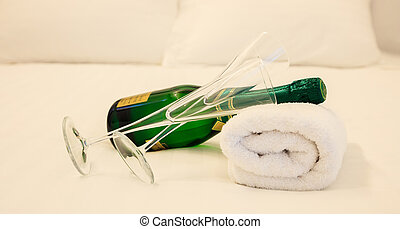 Champagne's bottle and couple of glasses laying on white towel. White bedding backdrop, closeup view