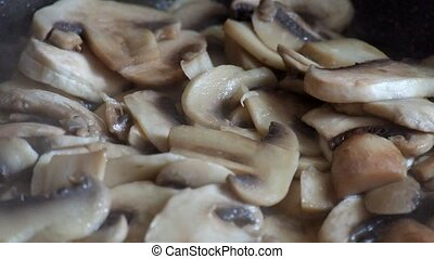 Champignon mushrooms are fried in a frying pan
