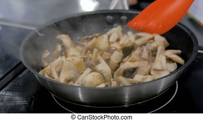 Champignon mushrooms frying and sizzling in pan - Chef hand...