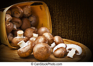 Champignon mushrooms with brown variety on wooden table (or board) scattered out of the basket