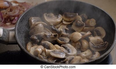 Champignons are fried in a pan. Steam rises. - Champignons ...