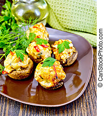 Champignons stuffed meat in brown plate on board