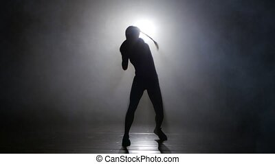 Champion boxer in the smoke sends kicks. Silhouette. Lights rear. Black background