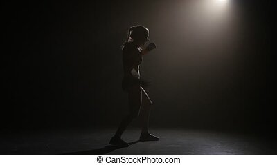 Champion boxer sends the punches. Silhouette. Lights rear. Black background. Side view