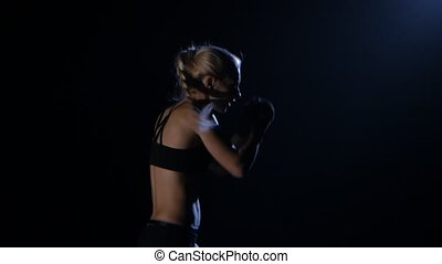 Champion kickboxer sends the punches. Silhouette. Black background. Side view