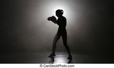 Champion kickboxer smoke evades counter punches. Silhouette. Black background . Side view