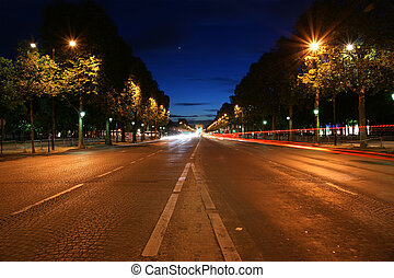 Champs-Elysees avenue at night with the Triumphal Arch in...