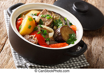 Chanakhi is a traditional Georgian dish of lamb stew with tomatoes, aubergines, potatoes, greens and garlic close-up. Horizontal