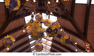 Chandelier is richly decorated with garlands made from artificial flowers.