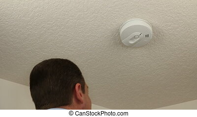 Adult man changing the 9-volt battery in his home ceiling fire alarm to protect his family from danger.