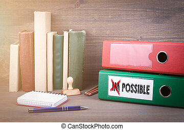 Change impossible to possible. Binder on desk in the office. Business background