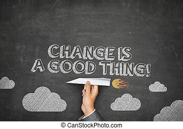 Change is a good thing concept on black blackboard with businessman hand holding paper plane