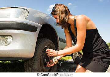 Changing a tyre - Young woman changing a flat tire on her...