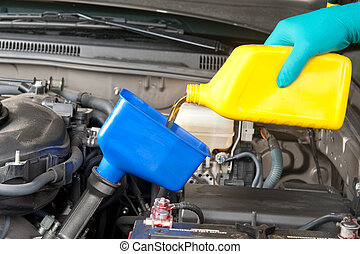 Changing automobile oil - An automotive mechanic changes the...