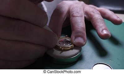 Changing battery in a quartz wrist watch at repair shop clip