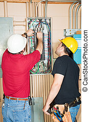 Electrician and apprentice changing out a faulty circuit breaker in an industrial panel.