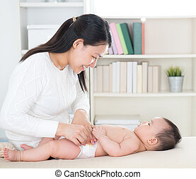 Changing diaper - Asian mother changing diaper to baby girl ...