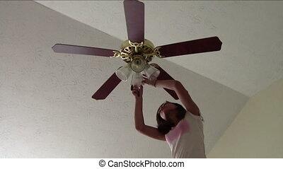 Teen changing light bulbs in ceiling fan