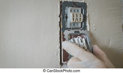 Changing room wall light switch installation with a screwdriver, close-up electrician hands.