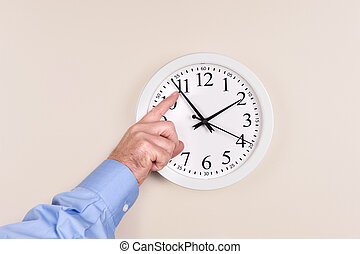 Changing time - A man changes the time on a clock, moving it...