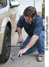 Changing Tire - A mechanic changing a tire.