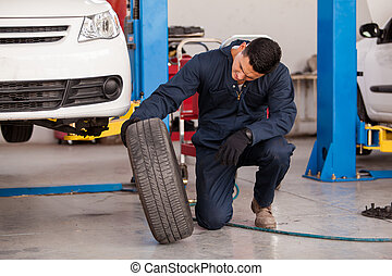 Changing tires at an auto shop - Young mechanic inspecting a...