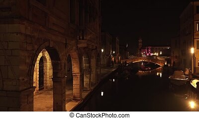 Tranquil channel near embankment with historical arch passage with stone columns in Chioggia city in dark autumn evening