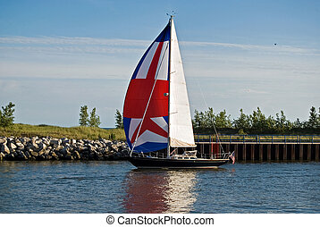 Channel Sail - Colorful sail on boat in harbor waterway.