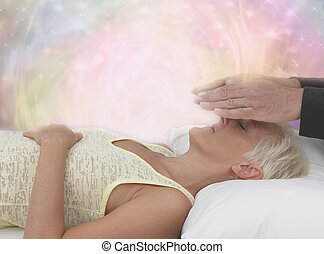 Channeling Healing Energy - Female patient lying with eyes...