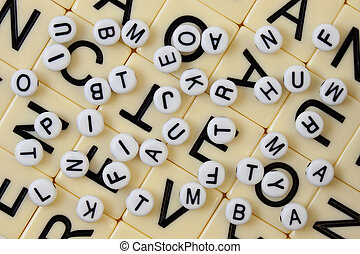white beads with black letters spilled randomly on an ivory mosaic with bigger letters
