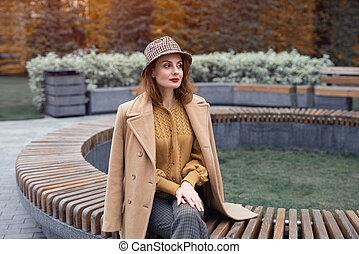 chapéu, francês, ou, xadrez, esperando, banco, flowerbed, mulher, charming, tingido, agasalho, girlfriends., data, senta-se, jovem, redondo, dela, foto, bege, outono