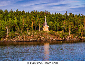 Chapel by the river among the trees