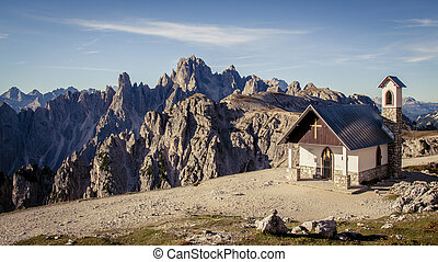 Chapel of the Alpini in the Italian Dolomites on a clear blue sky day. Mountains and Alpine scenery in the background.