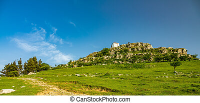 Chapel on top of the hill under blue sky