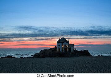 Chapel Senhor da Pedra at night in Miramar Beach, Portugal.