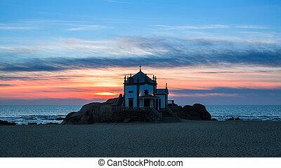 Chapel Senhor da Pedra at sunset, Miramar Beach in Porto, Portugal.