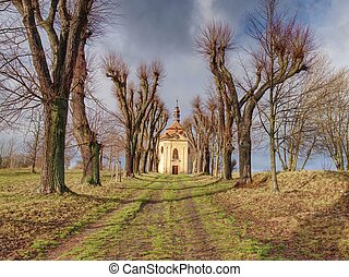 Chapel with autumn trees at end of alley road