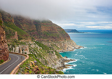Chapman's Peak Drive, Cape Town, South Africa. Rough coastline in winter season, cloudy and dramatic sky, waving Atlantic Ocean.