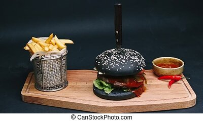 Charcoal burger with french fries and red sauce are on the...