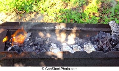 charcoal fire grill, close up with flames burn fire on the...