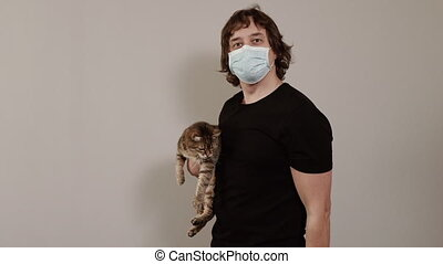 Charging at home. A man in a protective mask exercises at home during a virus pandemic.