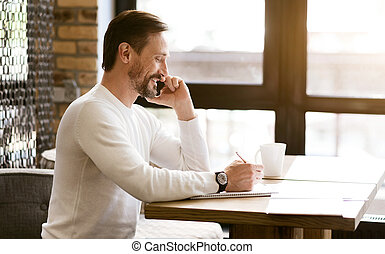 Charismatic bearded man talking over the phone in the cafe