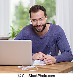 Charismatic bearded man working at a desk