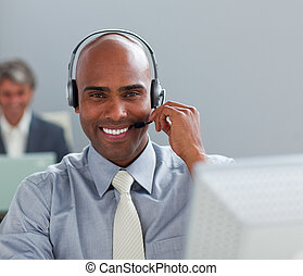 Charismatic  businessman with headset on working at a computer