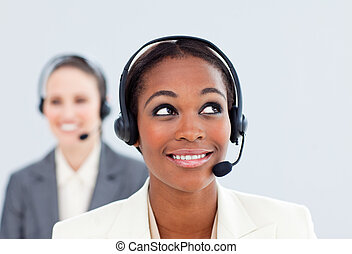 Charismatic businesswoman and her colleague with headset on...