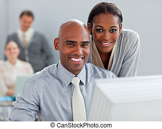Charismatic businesswoman helping her colleague at a computer