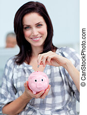 Charismatic businesswoman saving money in a piggy-bank at her desk