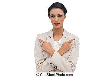 Charismatic businesswoman with her arms crossed and fingers point