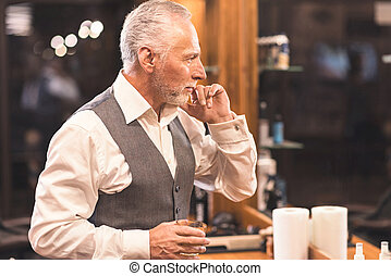 Charismatic client examining his appearance after getting haircut in barbershop